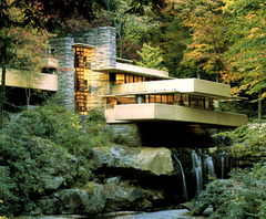 Frank Lloyd Wright's Fallingwater cultivates an organic relationship between the building and its location by: